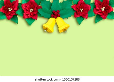 Garland of paper poinsettia flowers and Christmas bells with holly branch. Paper art and craft in festive design. Volumetric paper objects handmade. Minimal Christmas concept