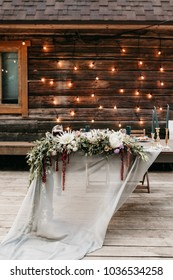 Garlands of wedding lights on the wooden wall and festive table served dishes