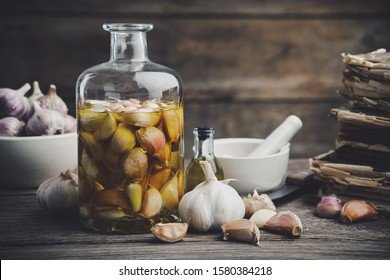 Garlic aromatic flavored oil or infusion bottle and garlic cloves. Mortar, old recipe books, kitchen knife. Garlic cooking.