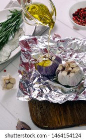 Garlic baked in foil with salt, spices and olive oil. Roasting garlic in olive oil in foil with sprigs of rosemary, on wooden background