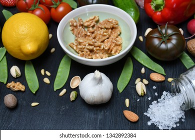 A garlic, a bowl with walnuts, a lemon, a pepper, tomatoes, a radish, a cucumber,Romaine,walnuts,pine nuts,pistachios,almonds,nutmeg,a pea pods & a glass jar with spilled salt lying on a black surface