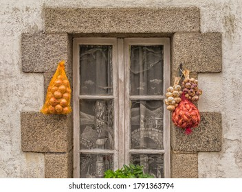 Garlic braid and onions hanging on old window for direct marketing