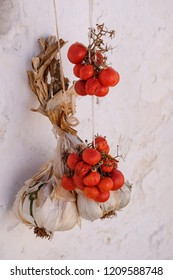 Garlic and bright red tomatoes hung out to dry outside a house in Alberobello, Puglia, Italy.