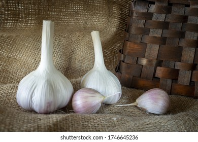 Garlic bulbs and cloves in close-up on brown sack cloth