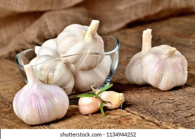 Garlic bulbs and cloves in glass places on rustic wooden boards