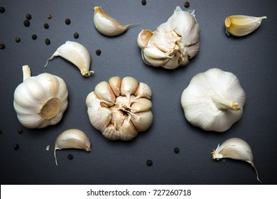 Garlic bulbs and garlic cloves on black background