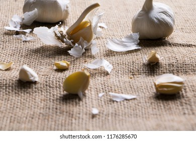 Garlic bulbs and Garlic cloves on tissue, rustic background