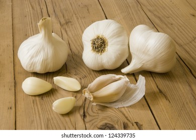 Garlic bulbs and cloves, over head view on pine wood table