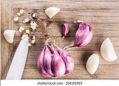 Garlic bulbs on wooden chopping board