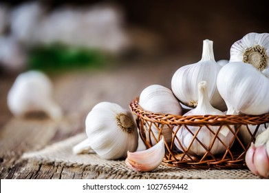 Garlic bulbs in wooden basket on rustic old table. Fresh gralic cloves. Pile of garlic on jute.