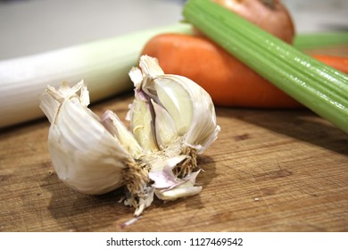 Garlic with carrot and celery on chopping board, vegetables on wooden cutting board