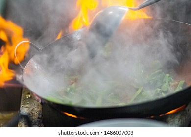 Garlic and chilli with a raw pork stir fried on a vegetable oil in a black hot pan in kitchen, The restaurant chef on the street is cooking. How to cook main food in Thailand