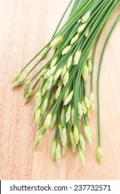 Garlic chives on wooden background