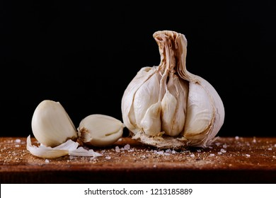 Garlic cloves with added spices broken up and ready to be used on a wooden board and black background