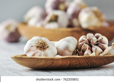 Garlic cloves and  bulb in wooden bowl. Healthy food.