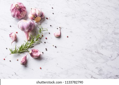 Garlic Cloves and Bulbs with rosemary salt and pepper on white marble board.