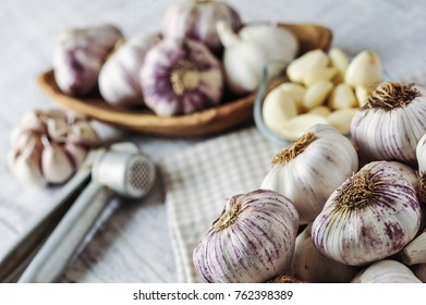 Garlic cloves and bulbs in wooden bowl
