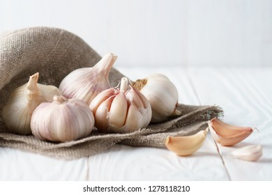 Garlic and garlic cloves on canvas and white rustic wooden table.
