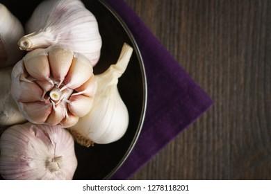 Garlic and garlic cloves on dark backround.
