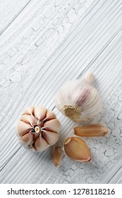 Garlic and garlic cloves on white rustic wooden table.