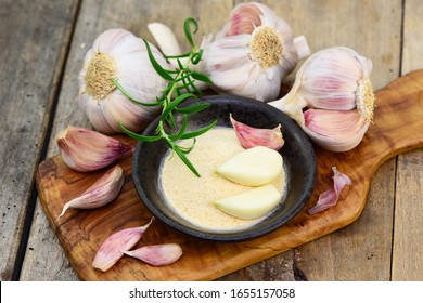 Garlic cloves on a wooden kitchen table, fresh and dry, closeup