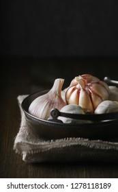 Garlic and garlic cloves in selective focus on dark background.