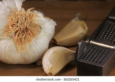 Garlic, cloves of garlic and a vintage metal garlic press on a bamboo cutting board.