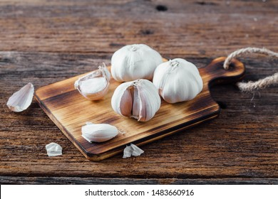 garlic with cutting broad on wooden background