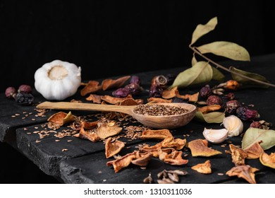 Garlic, dried fruit and seeds in dark rustic background. Artistic photo of garlic and dry fruit on old black table shot in low key ciaroscurro style
