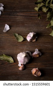 Garlic and dry bay leaves on a wooden table, top view