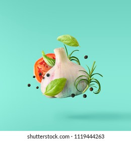 Garlic falling in air with pepper and herbs like rosemary and basil leaves on turquoise background. Spicy food concept