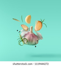 Garlic falling in air with pepper and herbs like rosemary on turquoise background. Spicy food concept