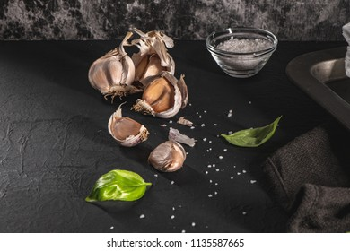 Garlic and fresh basil leaves on kitchen countertop. Concept of mediterranean traditional healthy food.