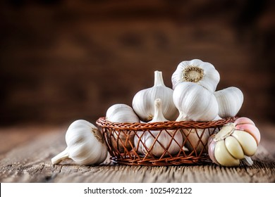 Garlic. Fresh garlics in wooden basket. Pile of spice cloves.