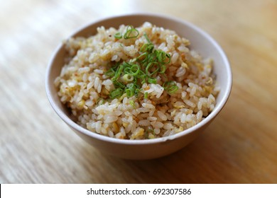 Garlic fried rice with spring onion vegetables on top in bowl - Japanese food