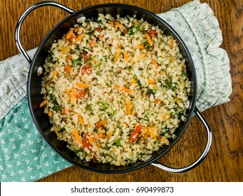 Garlic and Ginger Cauliflower Rice On A Green Napkin Against A Dark Oak Wooden Background