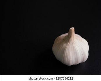 Garlic has a spigot on black background dark tone