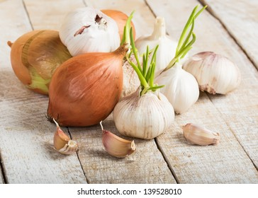 Garlic and onion on wooden background. Selective focus.