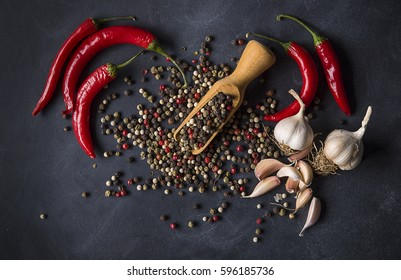 Garlic , peper and chili peppers on a dark background