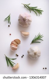 Garlic and rosemary on white background. Flat lay