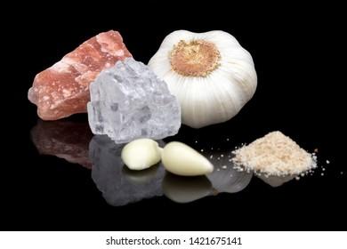 Garlic salt together with salt crystals and garlic cloves on a black background