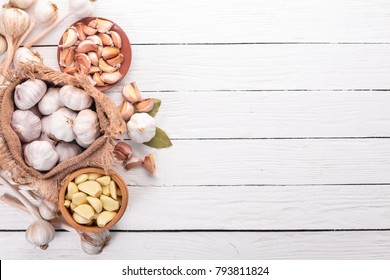 Garlic. A set of fresh garlic on a white wooden background. Top view. Copy space.