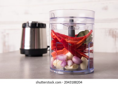 Garlic, shallots, pieces of red chili, and various other spices are placed in the electric food chopper container, before being pureed. The driving machine is behind it.