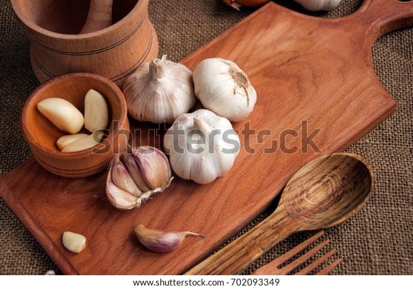 Knoblauch. Knoblauch in Scheiben, Knoblauch, Knoblauch in Holzschüssel auf Holzhintergrund auf Holzhintergrund. Platz für Text, Kopienraum Konzept der gesunden Lebensmittel.