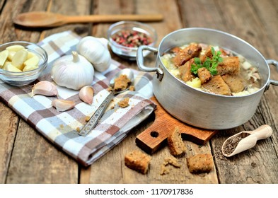 Garlic soup in an old saucepan, fresh garlic bulbs, cloves, colored pepper, wooden spoon, croutons and a towel on a rustic wooden table
