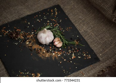 garlic and spices on a black background and smoke