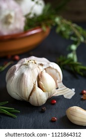 Garlic with sprig of Rosemary and Thyme in a clay dish