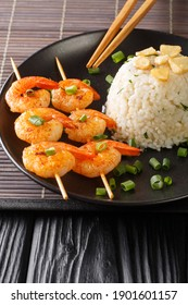 Garlicky and buttery, this simple Japanese Garlic Fried Rice topped with garlic chips with fried shrimps close-up in a plate on the table. - Shutterstock ID 1901601157