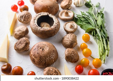 Garlicky mushrooms ingredients for baking portobello, cheddar cheese, cherry tomatoes and sage on white background,side view selective focus. - Shutterstock ID 1890038422