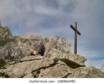 Garmisch-Partenkirchen, Germany, August 8., 2019: A blonde woman and a man with a backpack admire the mountains in Werdenfelser Land next to a simple wooden puritanical cross.